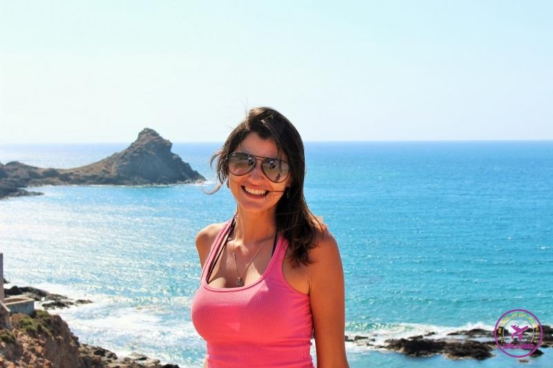 Mulher viajante sorrindo e atrás o mar do Cabo de Gata.