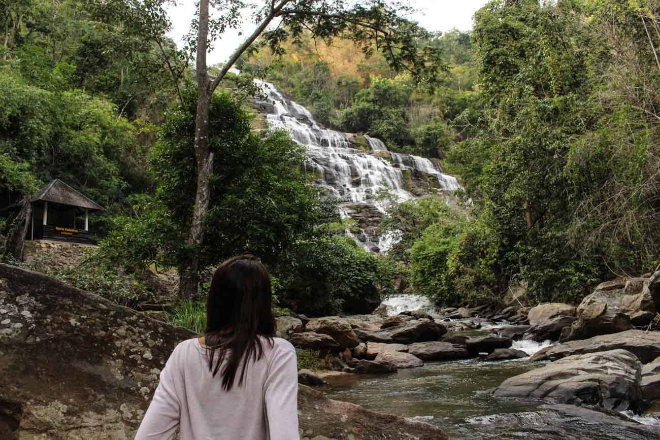 Woman looking at Mae Ya waterfall, in Chiang Mai, Thailand.