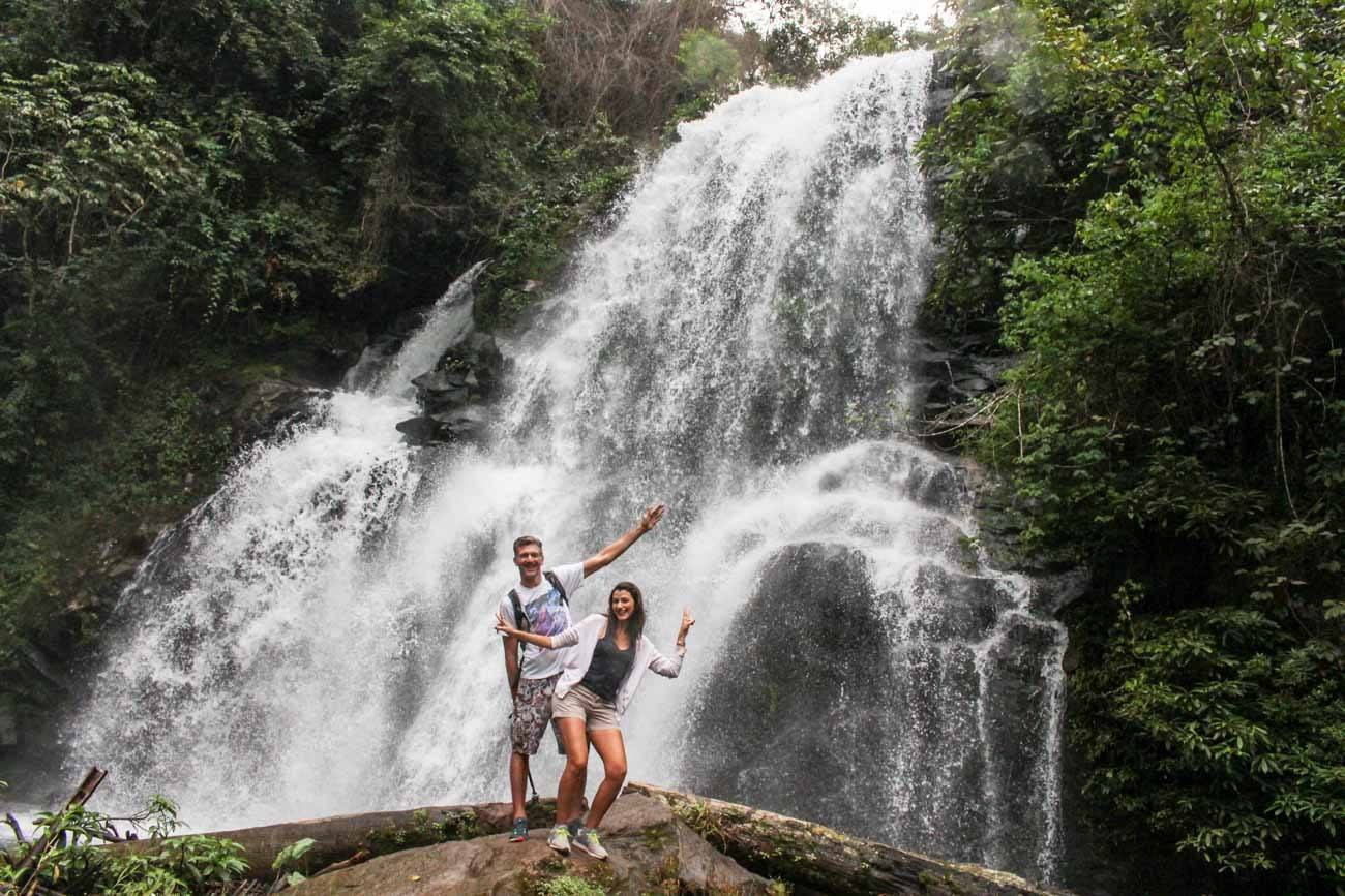 Couple of travelers having fun and posing for picture in front of Mae Ya waterfall..