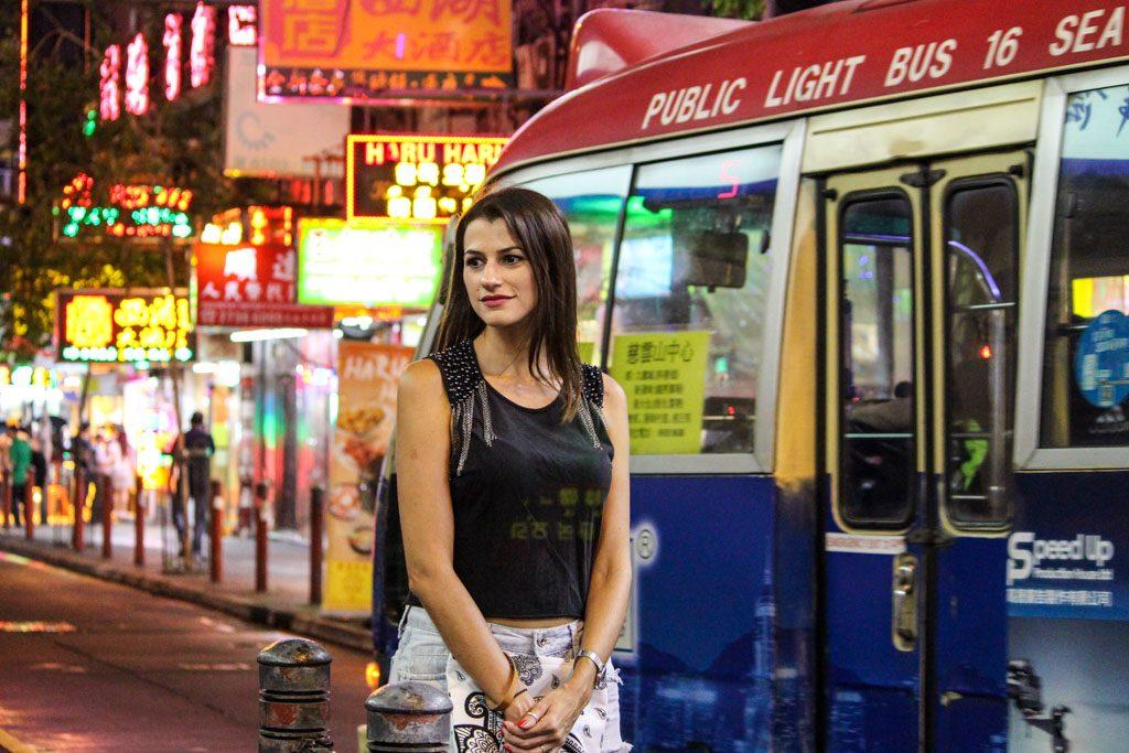 Dicas de quanto custa viajar na Ásia. Mulher esperando pelo ônibus em Hong Kong.