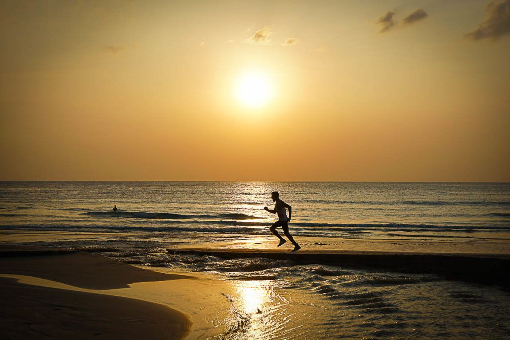 A man running on the beach as training to race the Ironman Thailand 70.3, in Phuket, Thailand.
