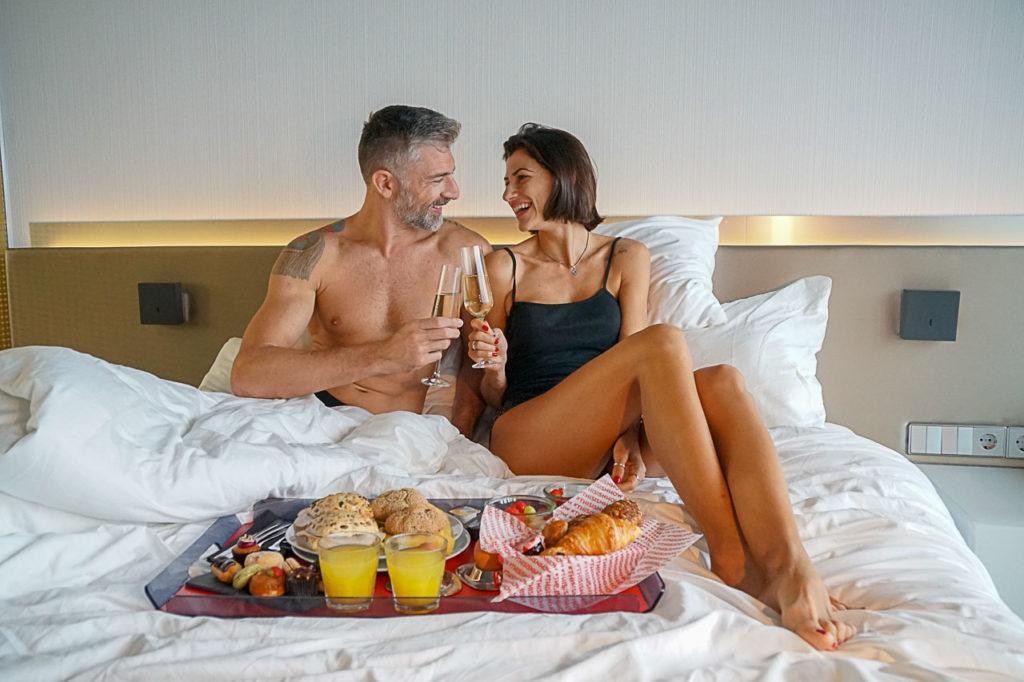O casal tomando café da manhã na cama do hotel são os escritores deste guia de hospedagem.