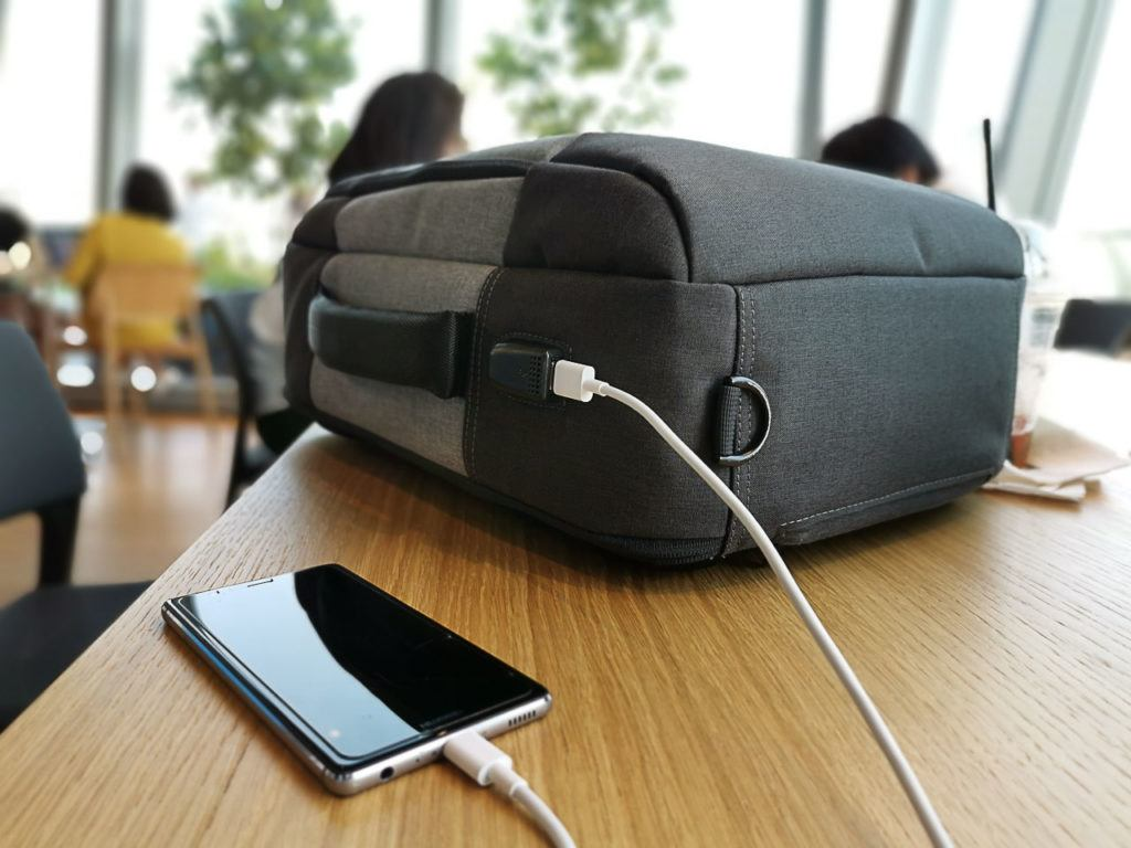 This modern daypack has a USB port on the outside which is connected to your power bank inside of it.