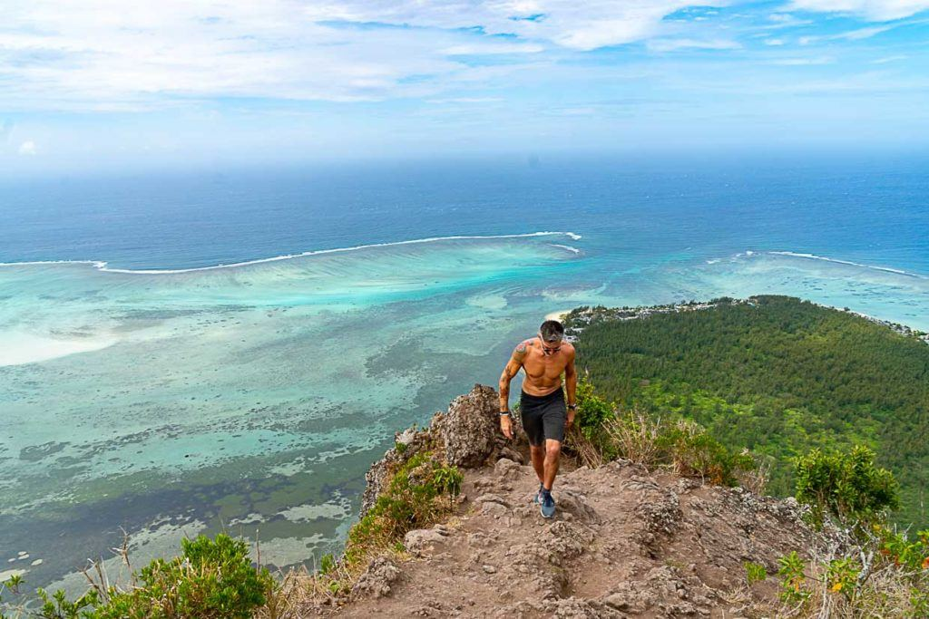 Man hiking to the top of a mountain in Mauritius.