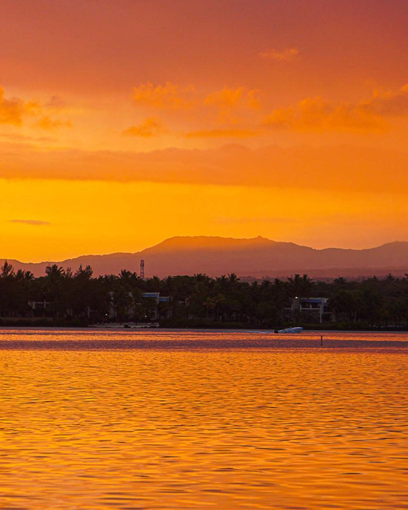 Sunset in Mauritius, photo shows the sky very yellow and the reflection of the clouds on the water.