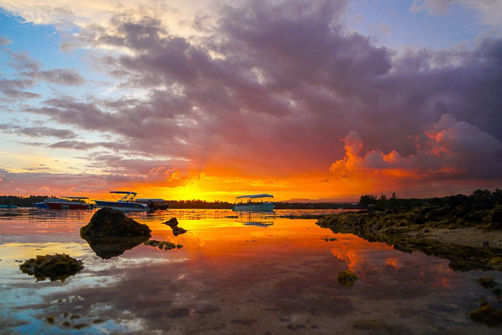 Sunset on a beach in Mauritius, with the sun reflection on the water.
