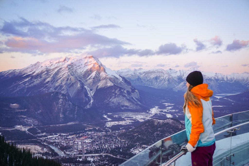 Traveler on a viewpoint admiring the snowcapped mountains.