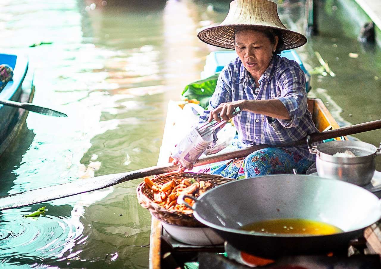 Photo of a floating market in Ayutthaya with a lady cooking on the boat.