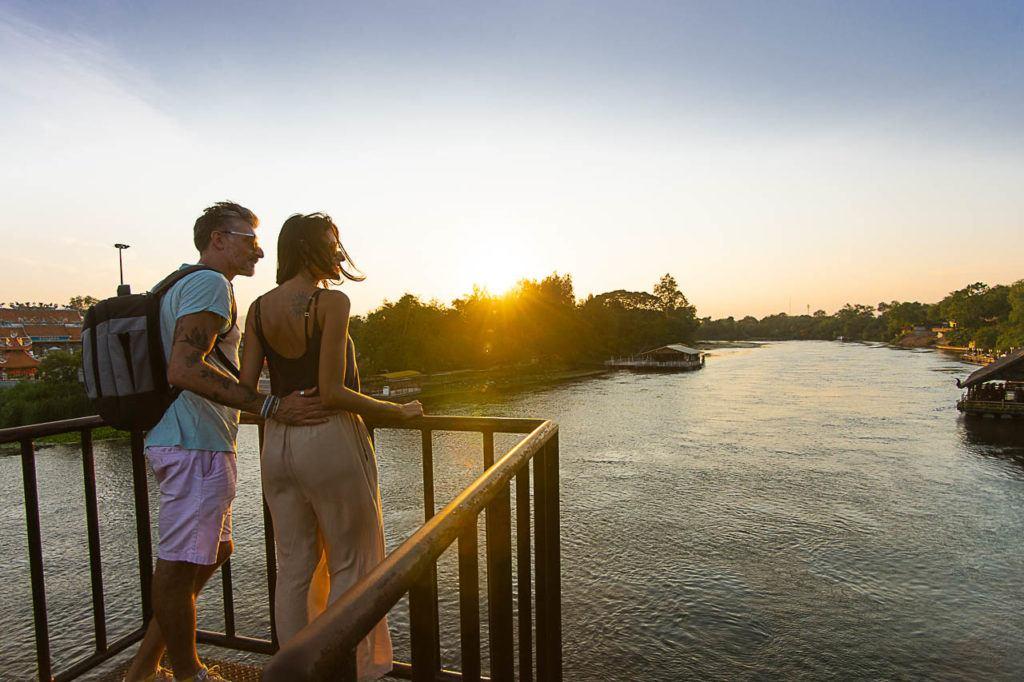 Casal sobre a ponte do rio Kwai em Kanchanaburi durante o pôr do sol.