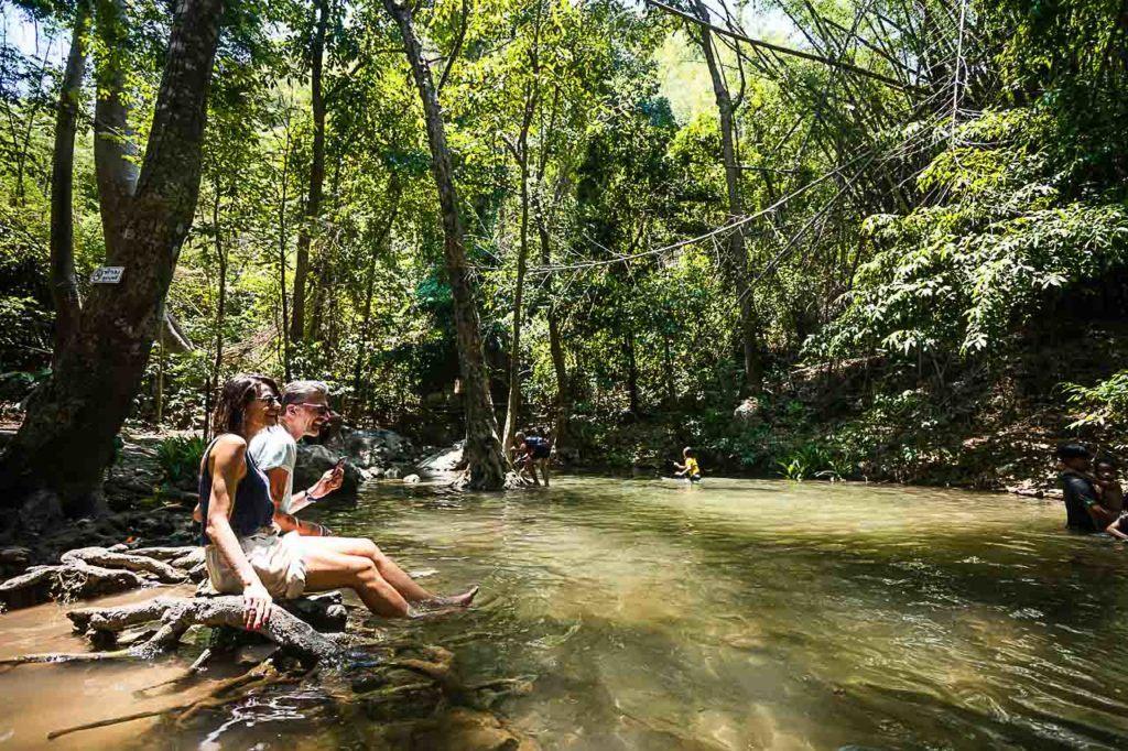 Viajantes e moradores locais se divertindo em uma piscina natural na Cachoeira Sai Yok.