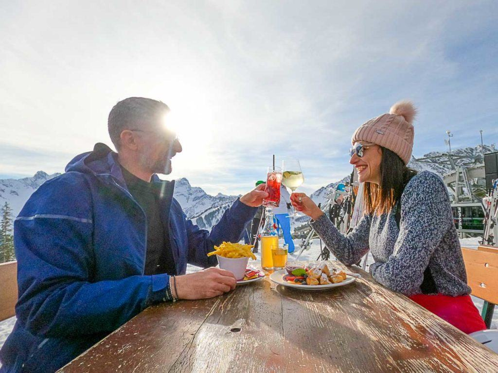 Ski couple making a toast at Frööd Restaurant, in Brandnertal.