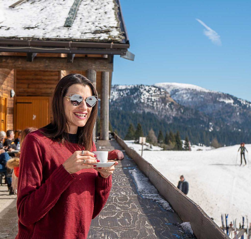 Traveler woman enjoying cup of coffee outside a restaurant in Folgaria Lavarone ski area, with snow and mountains around.