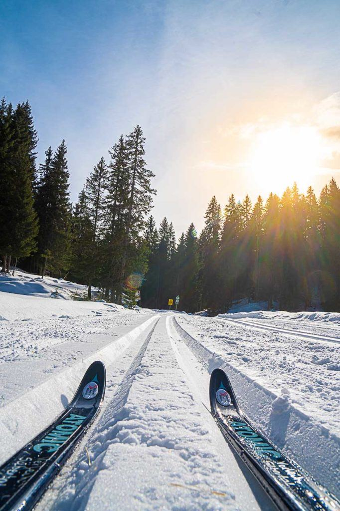 A pair of skis, a trail in the snow and the sun above.