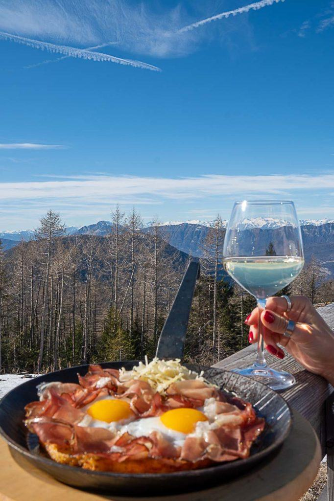 Padella Rustica, a glass of wine and a beautiful mountain view from the Rifugio Baita Tonda, a must-visit restaurant in Folgaria.