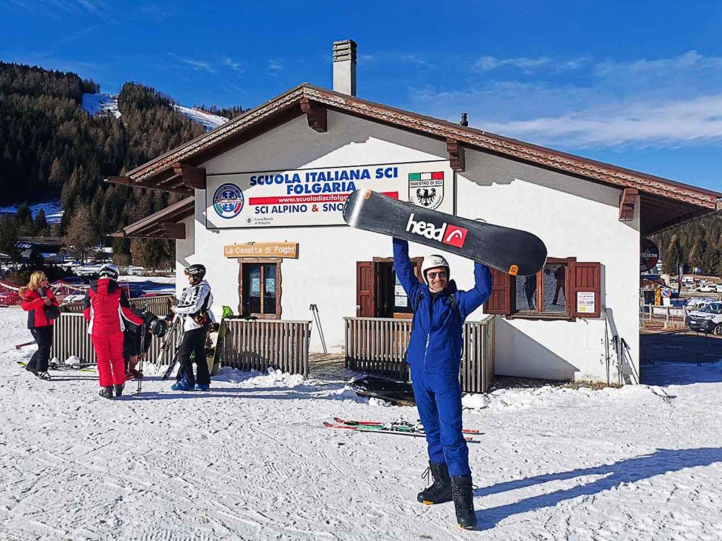 Man lifting a snowboard in front of winter sports school at Folgaria Lavarone ski area.