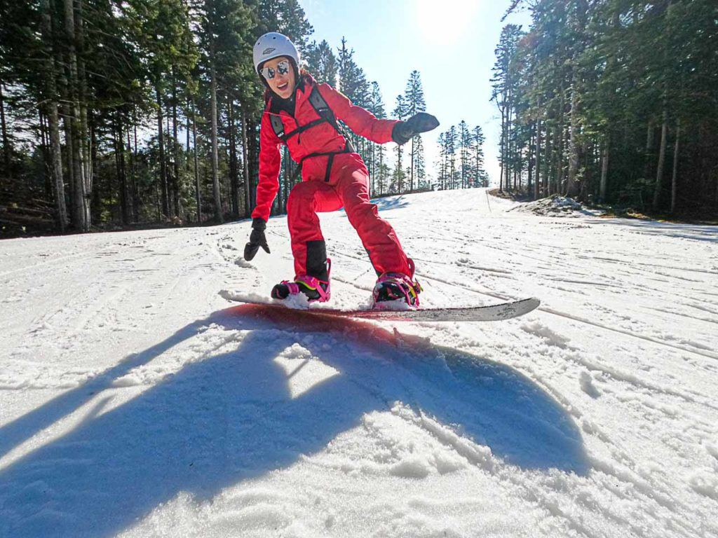 Woman practicing snowboarding at Folgaria Lavarone ski area.