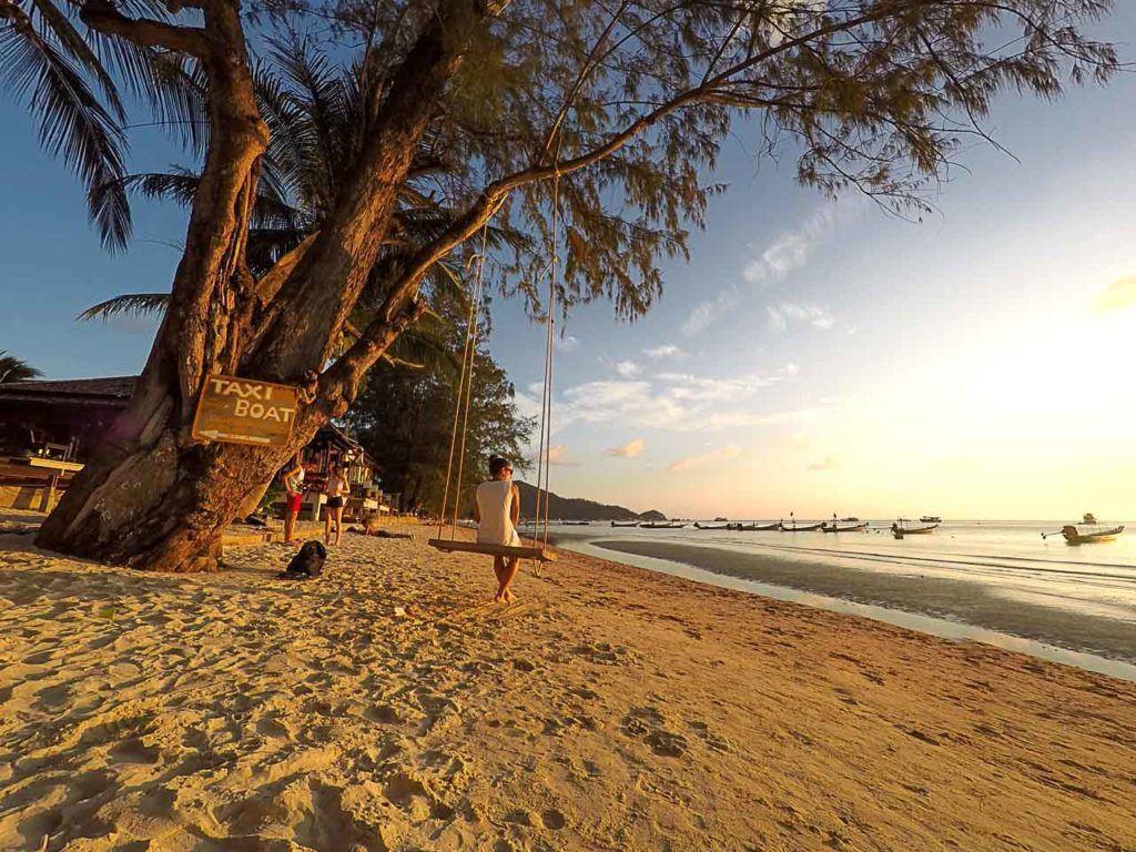 Mulher sentada no balanço da praia Sairee Beach em Koh Tao.