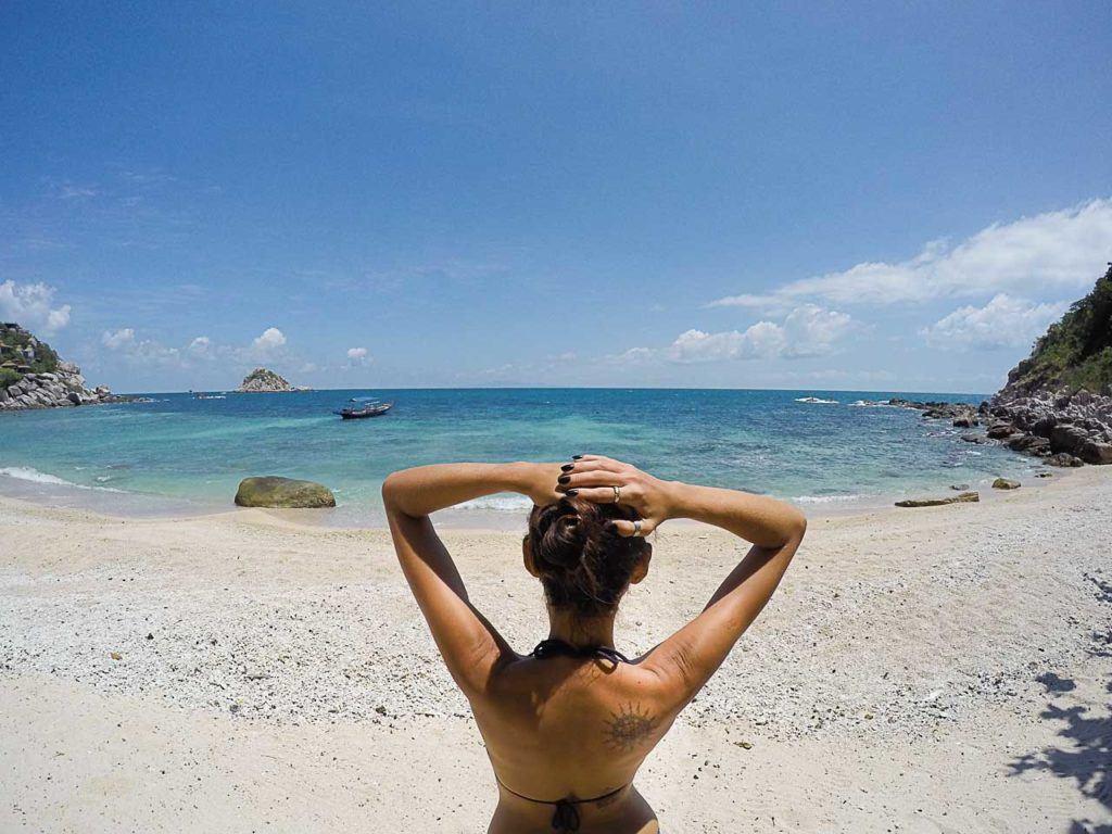 Mulher admirando o oceano em uma praia de Koh Tao.
