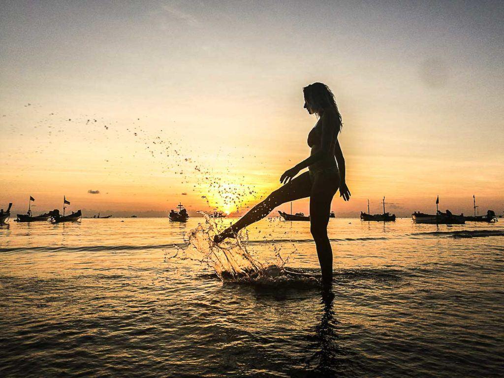Mulher sobre a água visitando as melhores praias de Koh Tao.