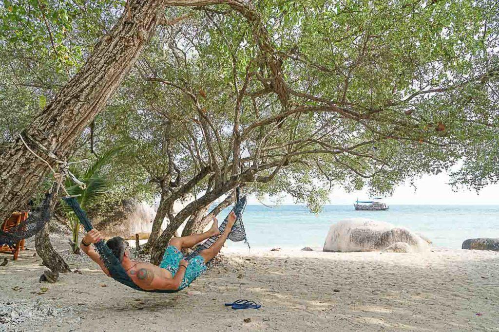 Homem descansando na rede em uma praia de Koh Tao, Tailândia.