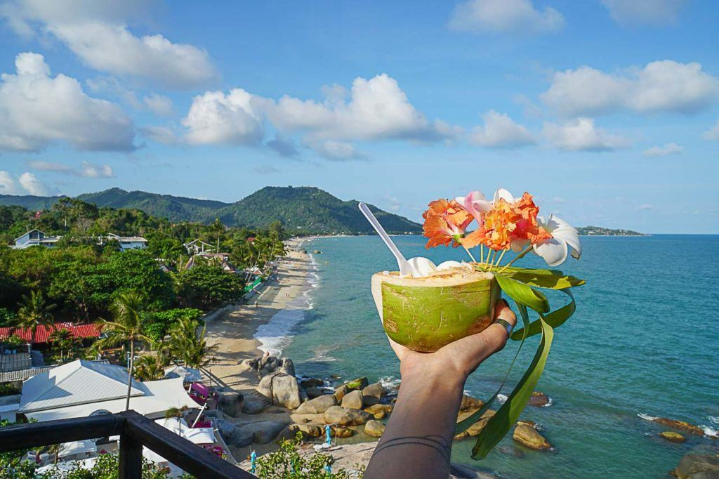 A coconut with flowers over a beach in Thailand. Find out with Love and Road all the best ways to get to Koh Samui.
