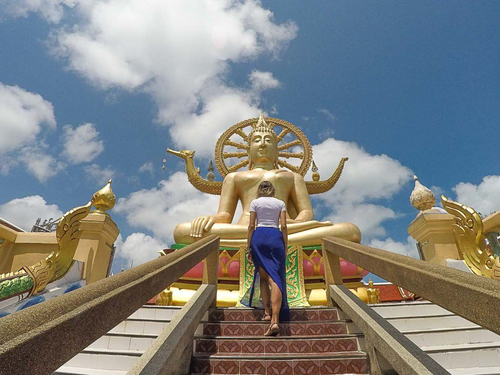 Woman climbing the stairs of Thai temple.