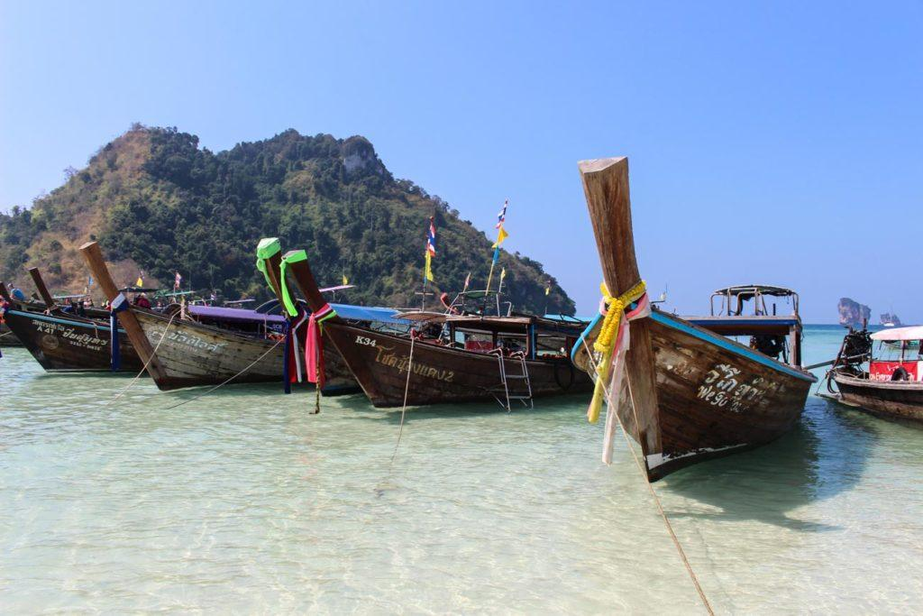 Thai longtail boats in Krabi's sea crystal clear water.