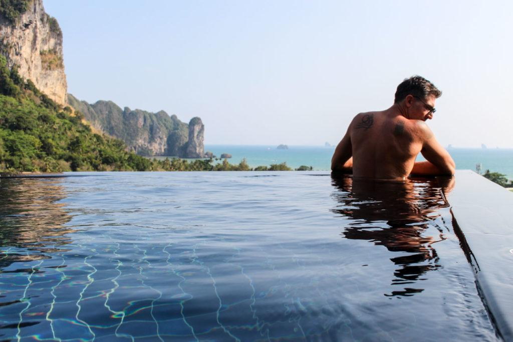 Man relaxing in an infinite pool. He is one of the travel bloggers of Love and Road.