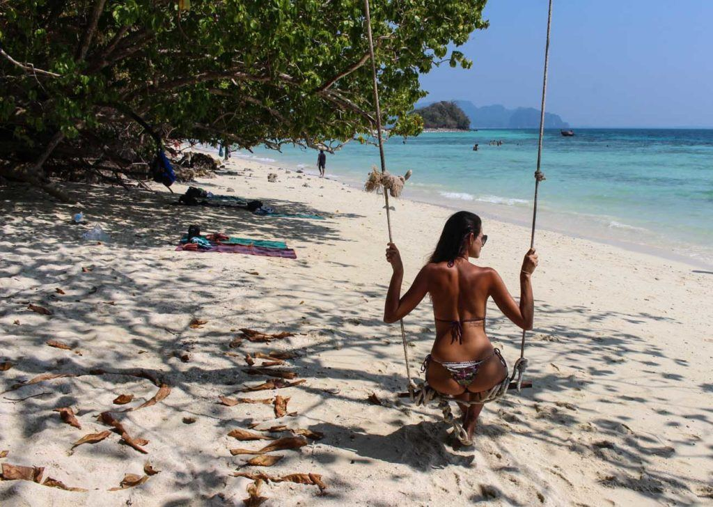 Woman on a swing on a beach of Thailand.