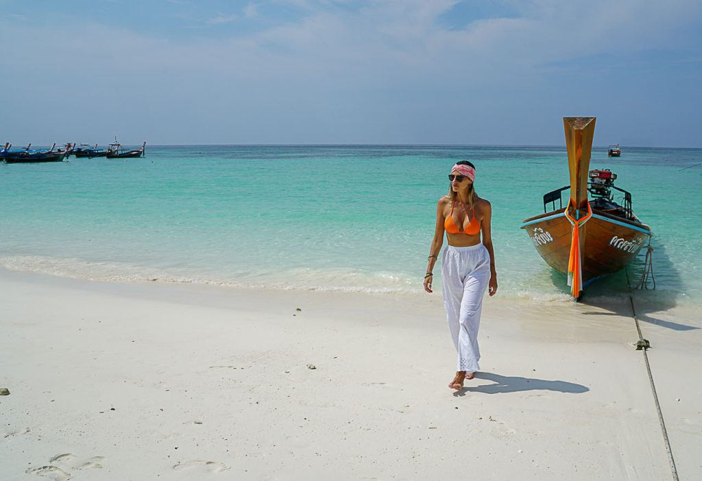Mulher caminhando sobre a areia em uma das melhores praias em Koh Lipe.