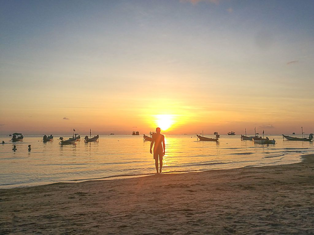 Man standing on the beach of Koh Tao admiring the sun.