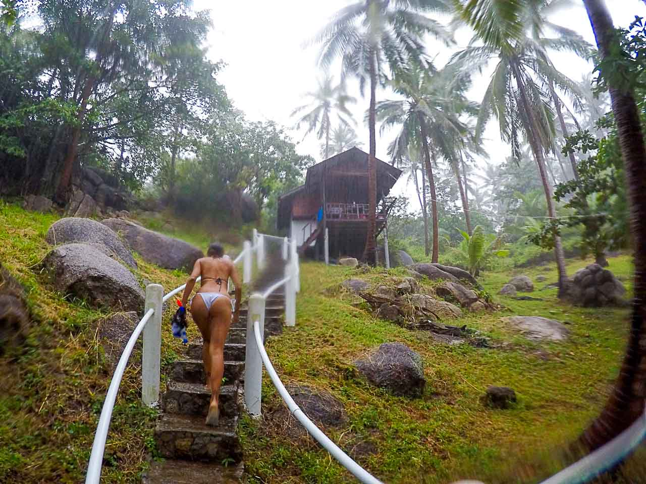 Woman climbing stairs to a bungalow in Chalok Bay.