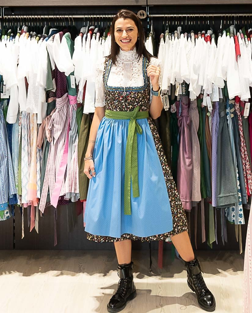 Woman trying on a Dirndl (a traditional Austrian dress) at Weintracht Shop, in Graz.