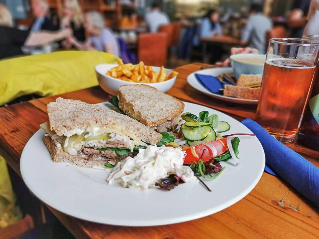 Um sanduíche, batatas fritas e cerveja sobre uma mesa em um bar. Planejando uma viagem para Inglaterra? Descubra aqui os custos de alimentação, acomodação e transporte no Reino Unido.