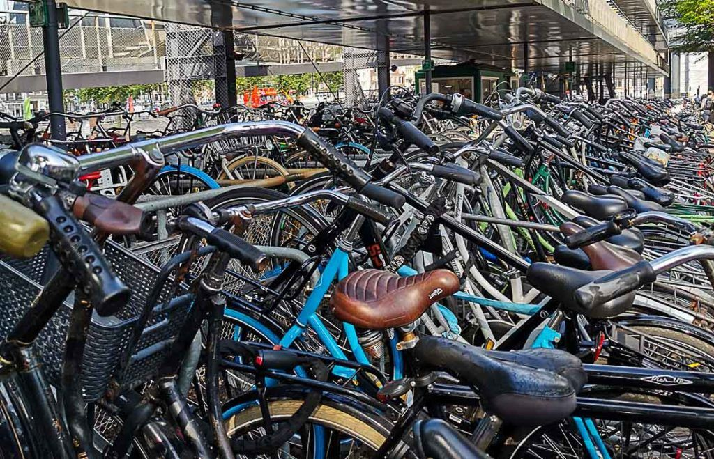Many bicycles at a parking area. Find here useful tips to plan your Amsterdam trip budget, we covered all trip costs in this post.