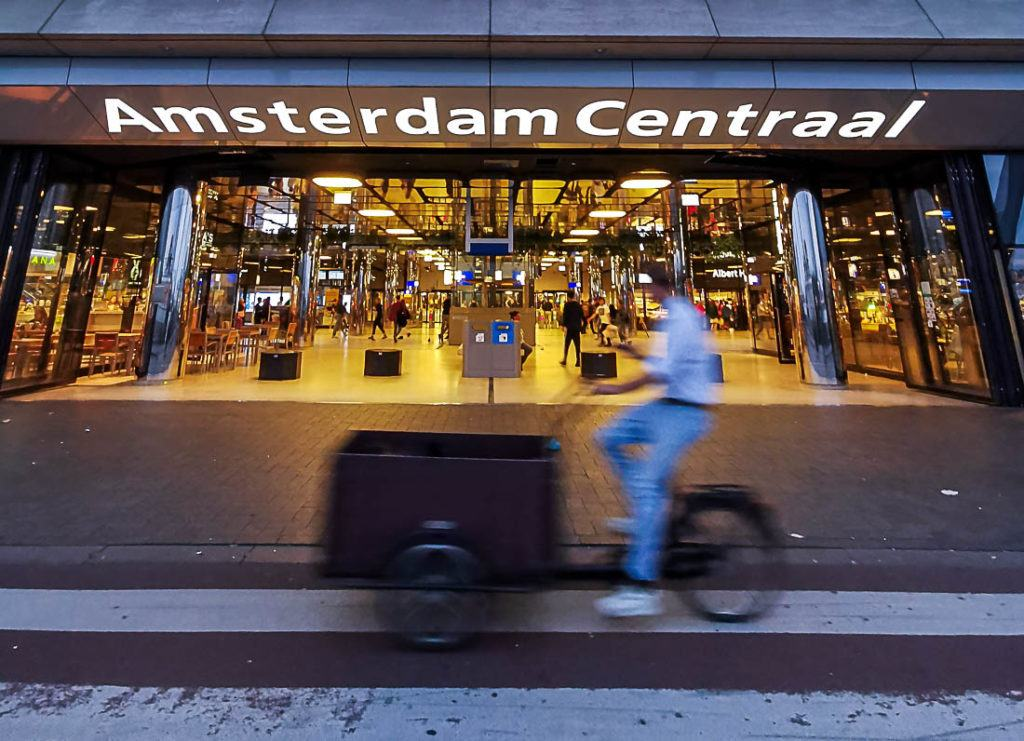 The entrance to Amsterdam Centraal. Discover all the information about the costs to travel to Amsterdam in this complete travel guide.