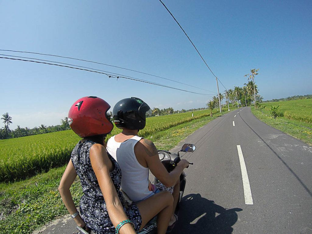 A Bali scooter ride through rice fields. This article will provide all information travelers need about getting around Bali and Bali activities.