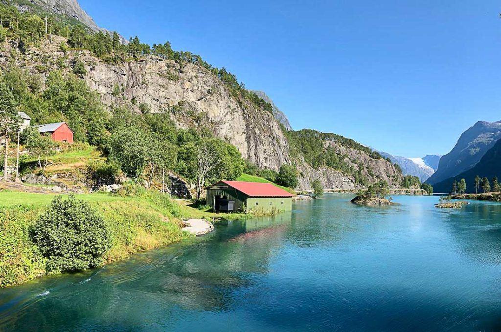 Uma casa à beira do lago na Noruega rodeada de montanhas. Explore este artigo e descubra todas as informações que você precisa para planejar seu orçamento diário para suas férias na Noruega.