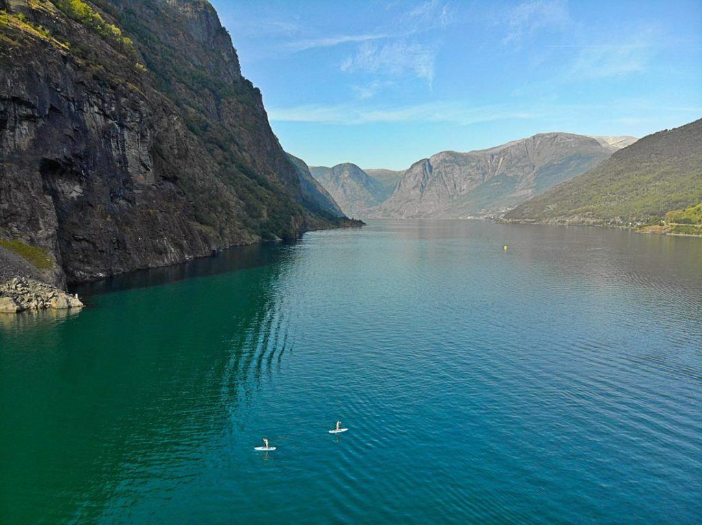 Duas pessoas remando de SUP em um lago em meio às montanhas da Noruega. Visitar as atrações e fazer passeios na Noruega é caro, mas há formas de economizar.