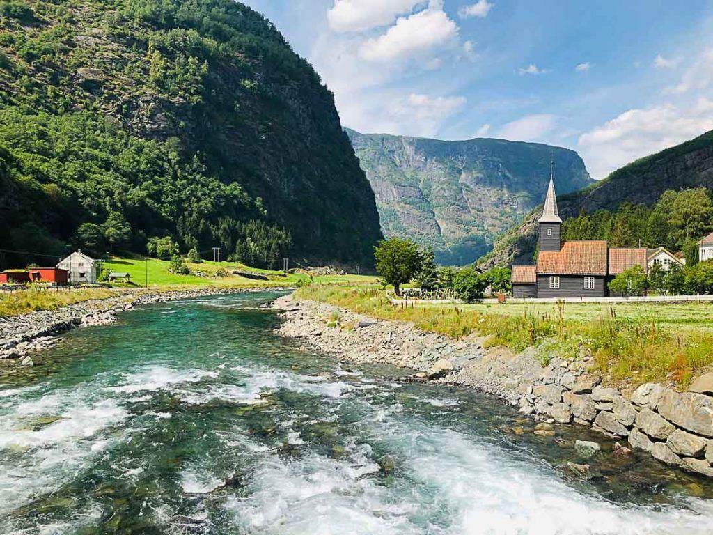 Rio, montanhas e uma igreja sob um céu azul. Planeje os custos de deslocamento pela Noruega com o auxílio deste maravilhoso guia de custo de viagem.