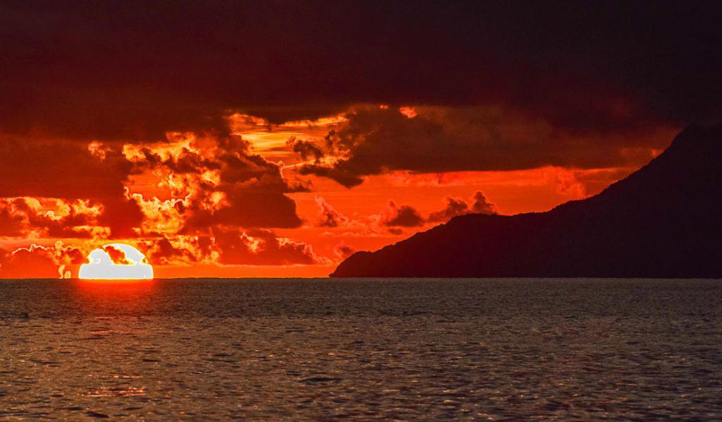 O sol se pondo no horizonte em Seychelles. Descubra aqui toda as informações que você precisa para planejar seu orçamento de viagem para Seychelles