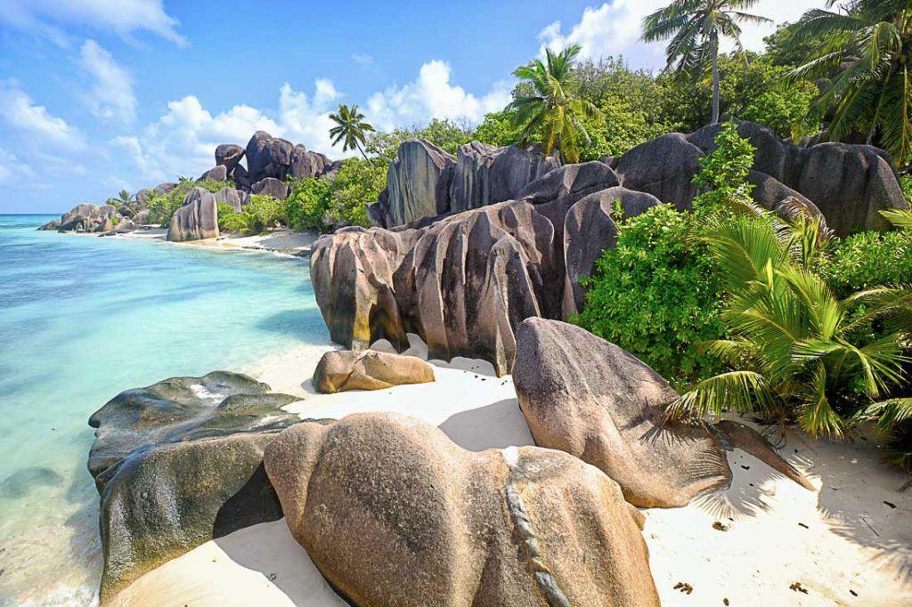 Praia de Anse Source d'Argent na ilha La Digue, Seychelles. Todos os custos de viagem para Seychelles estão neste artigo. Preços de alimentação, transporte, acomodação e mais.