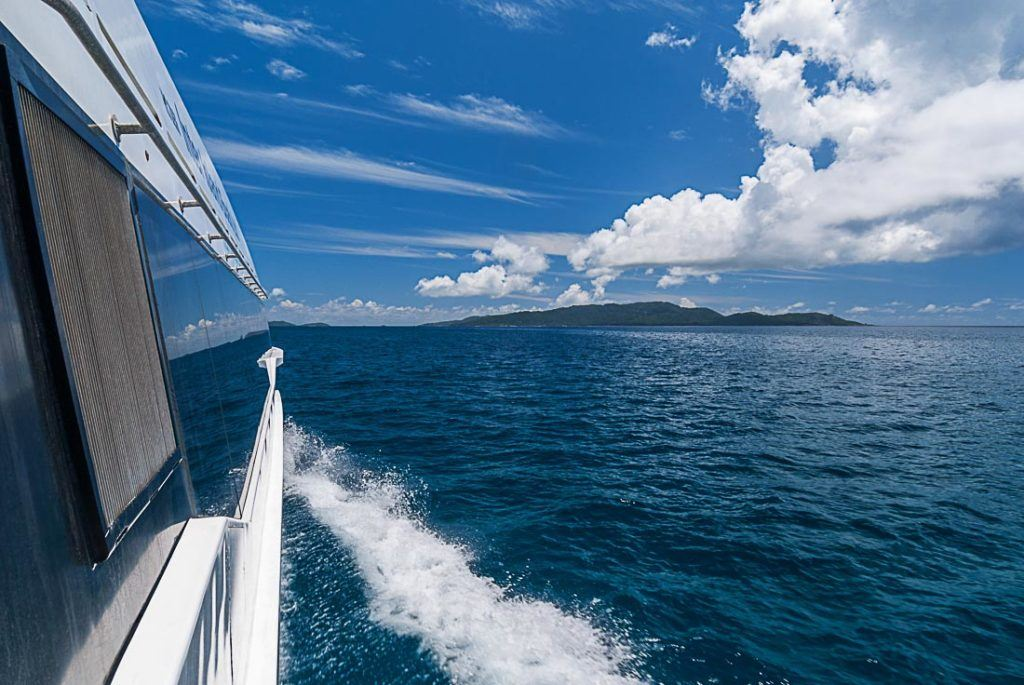 Uma foto tirada de um barco com uma ilha ao fundo em Seychelles. Planejando uma viagem para Seychelles? Encontre todos os custos de viagem para Seychelles aqui.