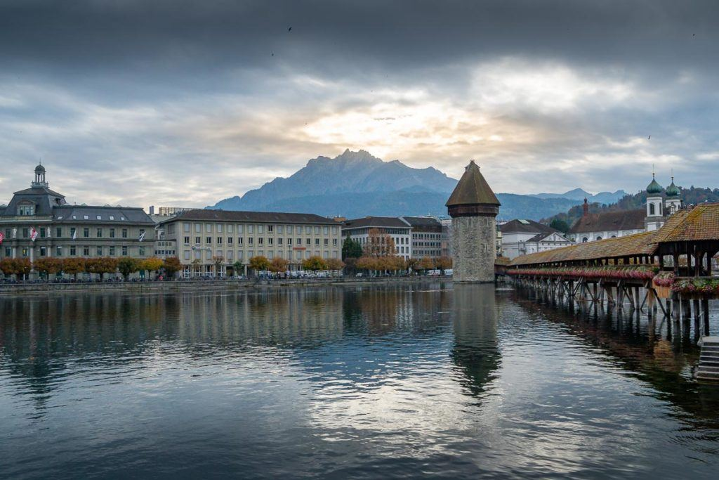 Some buildings, Kapellbrücke bridge, the river and mountains in the background in Lucerne, Switzerland.