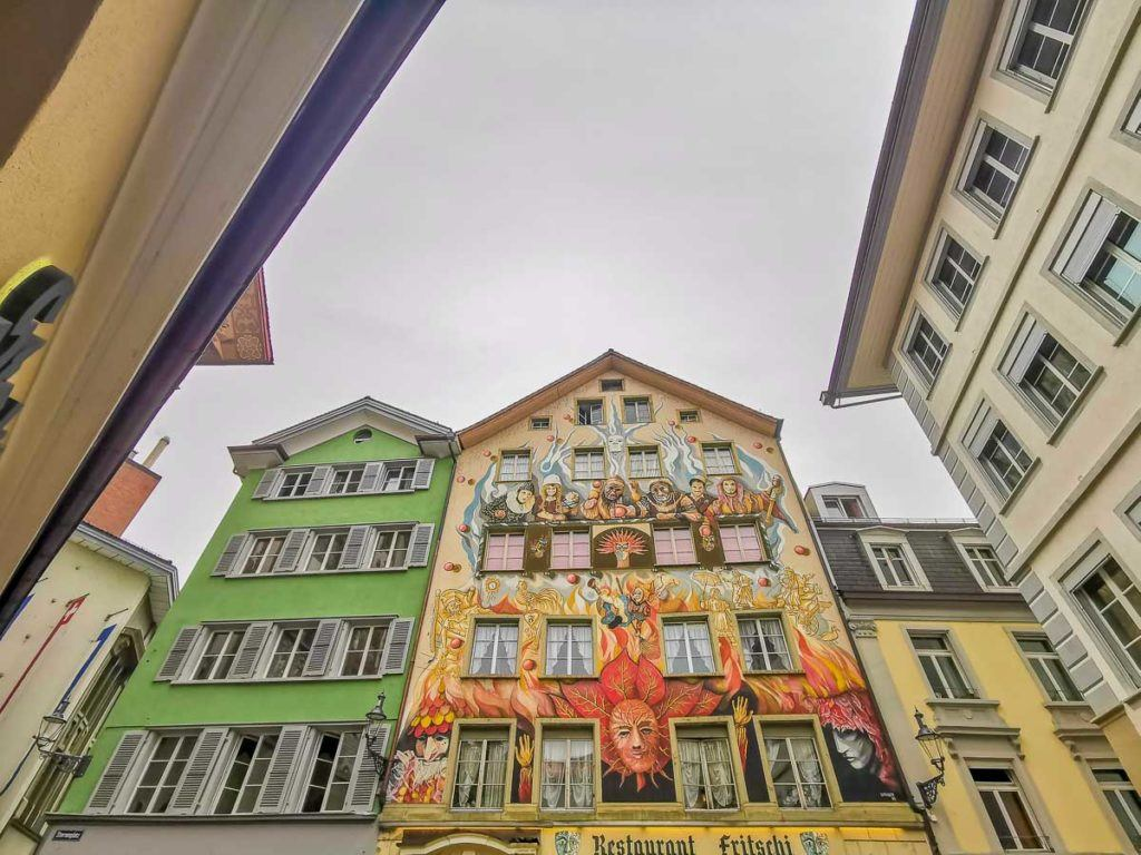 Old and colorful buildings covered with a mural.