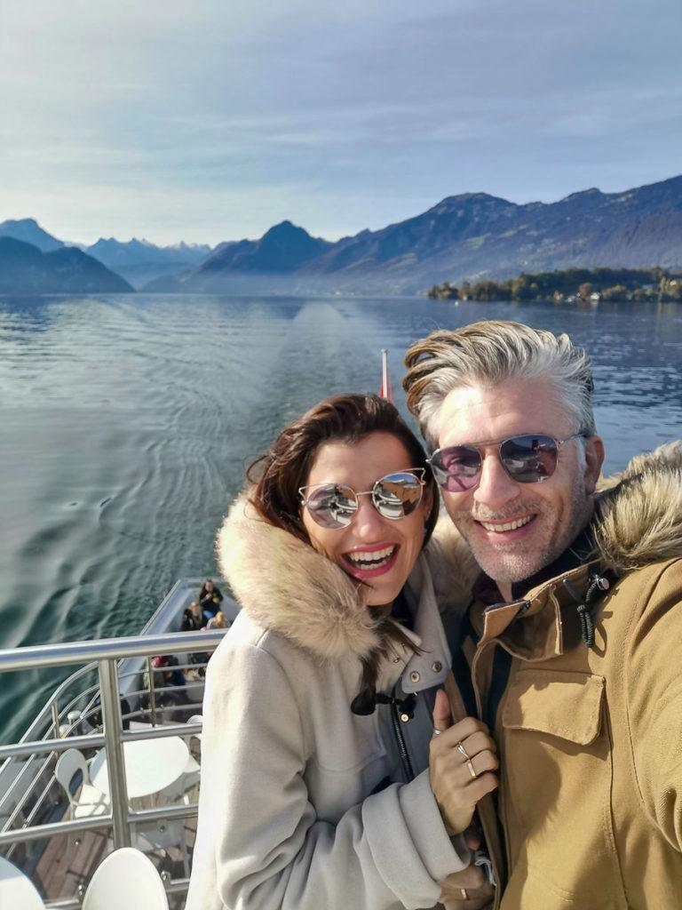 A selfie of a couple smiling on a boat cruise on Lake Lucerne.
